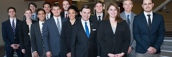a group of diverse students and business leaders standing shoulder to shoulder wearing suits