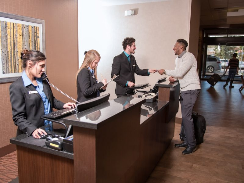 Three students, two females and one male, work behind the front desk of a hotel desk.