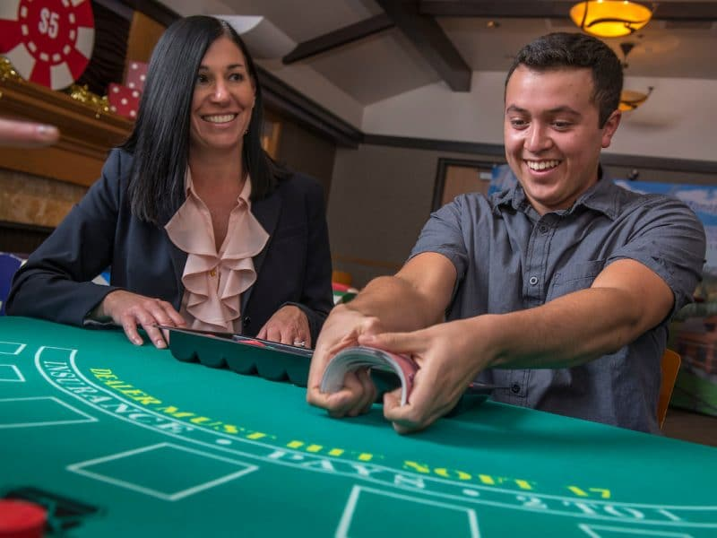 Close up of a NAU Casino Night blackjack table with a student dealer shuffling the cards.