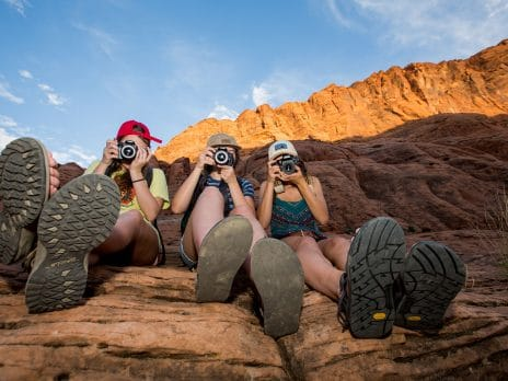 three people pose with cameras in front of their faces while perched on a rock at glen canyon