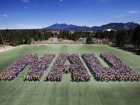 students form the letters N, A, and U on the football field