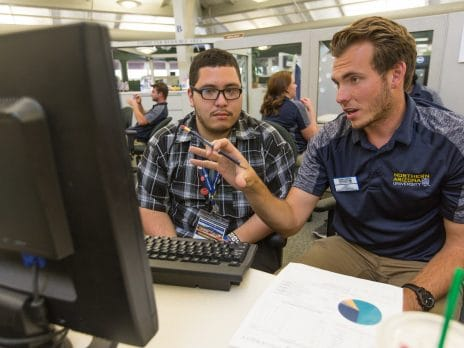 a man wearing an NAU staff polo assists another man