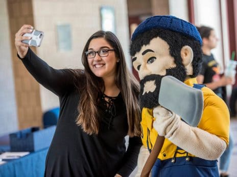 a student takes a selfie with the Louie the Lumberjack mascot