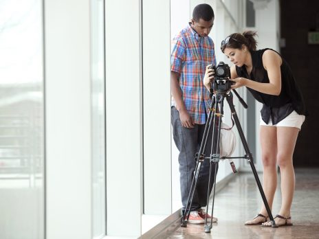 two members of a photography team adjust a camera on a tripod in a bright hallway
