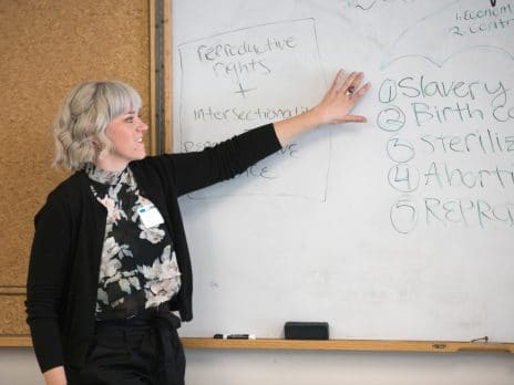 professor pointing to whiteboard covered in writing